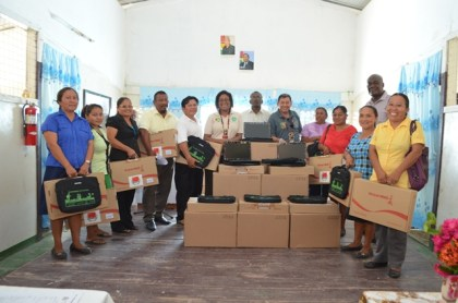 Fourth Vice President and Minister of Indigenous Peoples' Affairs, Sydney Allicock, Minister of Telecommunications, Catherine Hughes and Head, E-Governance Agency, Floyd Levi with some of the beneficiaries from the Deep South at the laptop distribution exercise at the Aishalton Secondary School