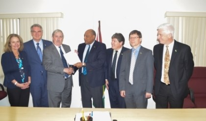 Minister of Natural Resources Raphael Trotman (centre) receives the letter of notification from Jeff Simons, Country Manager of ExxonMobil along with representatives from Nexen Energy and Hess Corporation at the Ministry of Natural Resources Boardroom, Brickdam
