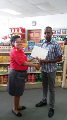 Shell Service Station Manager, Patricia Callender hands over the agreement to Bartica Mayor, Gifford Marshall