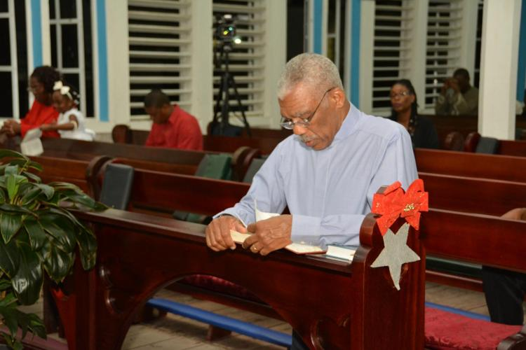 President David Granger kneels in reverence during the Christmas eve night service at the Christ Church Parish of the Anglican Diocese just before midnight