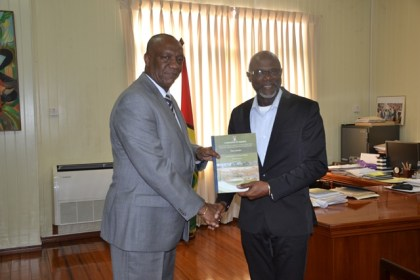 Minister of State Joseph Harmon receiving the final report into Puruni Mining Pit Collapse from Rear Admiral (ret'd) Gary Best at his office at Ministry of the Presidency today.