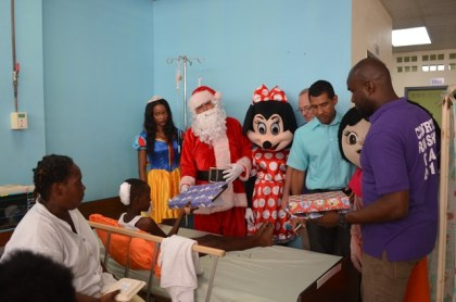A young boy collecting a present from Santa Claus and other Courts Guyana Inc. staff