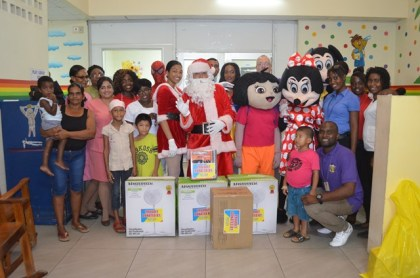 Santa and Mrs Claus posing with patients of the Paediatric Ward and staff of the Georgetown Public Hospital Corporation (GPHC), as well as staff of Courts Guyana Inc.