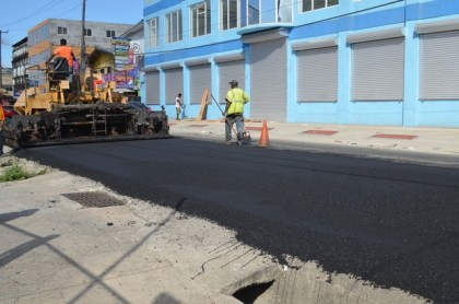 Workers from the Ministry of Public Infrastructure's Special Projects Unit applying asphalt on Lombard Street