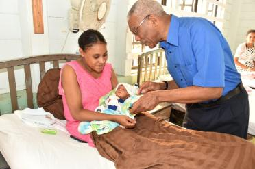 President David Granger giving this mother a special coin bearing the 50th Independence Anniversary commemoration logo
