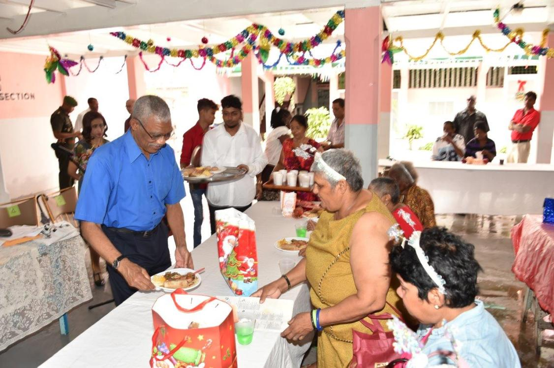 President David Granger serving Christmas lunch to residents of the Dharm Shala in Albouystown