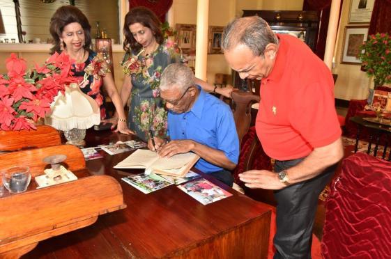 President David Granger signing the Dharm Shala's Visitor's Book while Mr. Edward Boyer, Ms. Kella Ramsaroop and Ms. Pamela Ramsaroop look on