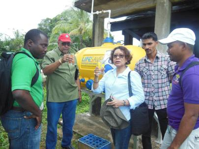GWI's Managing Director Dr. Richard Van West-Charles and Minister within the Ministry of Indigenous Peoples' Affairs, Valerie Garrido-Lowe tries the filtered water in Kamarang, as GWI's Hinterland Manager Osei Manifold (left), Doctor- in- Charge of Upper Mazaruni District Hospital - Amitraj Persaud (second right) & GWI's Planning and Implementation Director Ramchand Jailal (right) look on