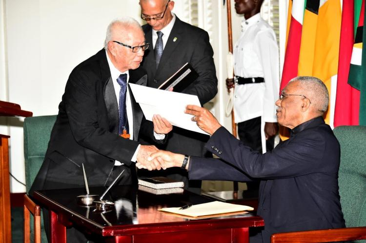 Chairman of the Lands Commission of Inquiry, Rev. George Chuck-A-Sang receiving his instrument of appointment from President David Granger
