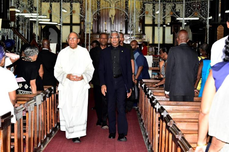 President David Granger is being escorted out of the St. George's Cathedral after the service by Reverend Andrew Carto