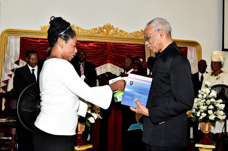 President David Granger being presented with a copy of the Andrews Study Bible by Deputy Vice Chancellor of the University of Guyana, Dr. Barbara Reynolds
