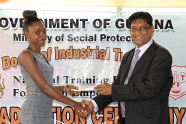 Andrea Benjamin an Information Technology student receiving her certificate from Member of Parliament of Region 6 Charran Dass