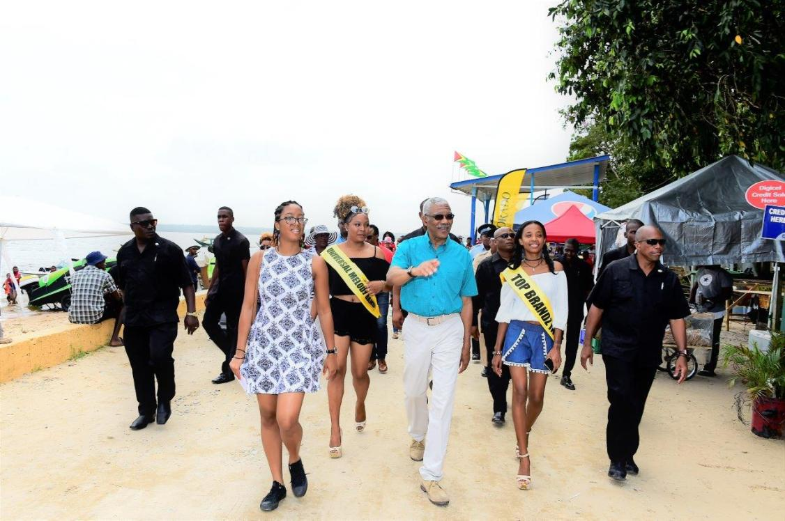 President David Granger takes a walk on the beach with his grand daughter, Ms. Athena Gaskin and two of the contestants in the Miss Bartica Regatta pageant