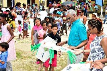 President David Granger is assisted by his grand daughter Ms. Athena Gaskin as he distributes kites to the children of Bartica