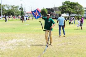 President David Granger was happy to help in raising a kite in the National Park on Easter Monday