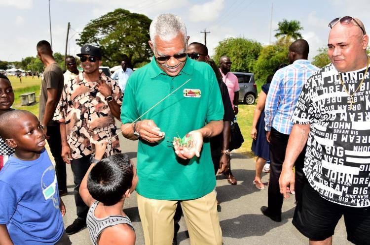 The smallest kite! President David Granger examines a tiny kite presented to him by a little boy during his walk through the National Park