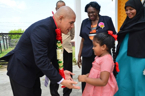 Minister of Social Cohesion, Dr. George Norton interacts warmly with Ms. Rihanna Sarah Williams, a five-year-old pupil of the Vryheid's Lust Nursery School after she welcomed him with a garland. Ms. Genevieve Allen, Chairman of the Regional Democratic Council (centre) and Ms. Natasha Singh-Lewis, Technical Officer attached to the Ministry (first, right0 are also pictured in the background