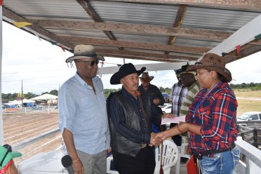 Minister Harmon and Vice President Allicock presenting the cheque for $1M to Ms. Rebecca Faria, Executive member of the Rupununi Rodeo Committee