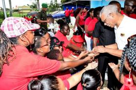 """President David Granger distributed special buttons with the words """"Every Child in School"""" to teachers at the GTU's Labour Day celebrations"""