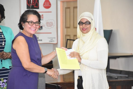 First Lady, Mrs. Sandra Granger presents graduate, Ms. Fatimah Ahmad Bacchus with her certificate