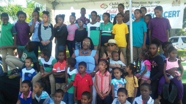 Minister of Social Protection Amna Ally and Minister with the Ministry of Natural Resources Simona Broomes with some of the children at the Family Fun Day