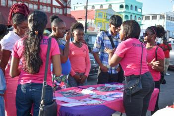 Persons at a booth speaking to Ministry of Public Health representatives on the HPV vaccine