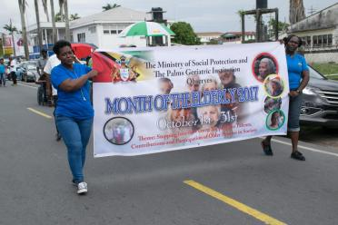 Participants in the walk carrying the banner announcing the start of the Month for the Elderly
