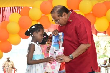 Prime Minister Moses Nagamootoo assists one of the children to unwrap her gift