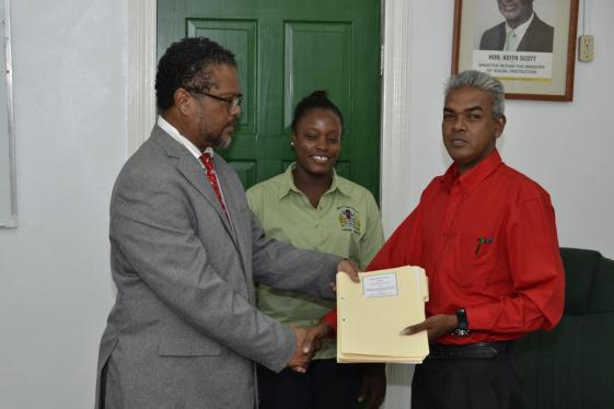 Charles Ogle, Chief Labour Officer, Ministry of Social Protection hands over the contractual agreement to the General Secretary of the National Association of Agricultural, Commercial and Industrial Employees (NAACIE), Dawchan Nagasar