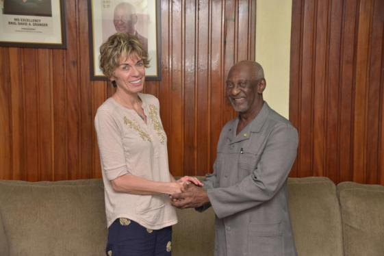 Hon. Keith Scott, Minister within the Ministry of Social Protection shakes hand with Claudia Coenjaerts, Director of International Labour Organisation as they agree to the signing of the Decent Work Country Programme