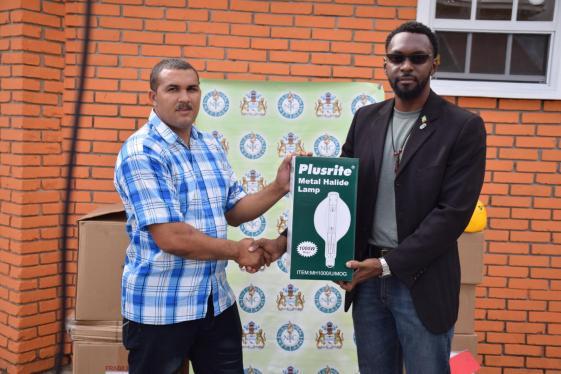 Director of Sport Christopher Jones handing over flood lights and sports gear to Chairman of Aranaputa CDC, Adon Jacobus