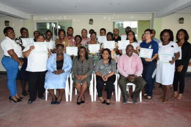 Director, Mental Health Unit, Dr. Util Richmond-Thomas (left), Minister within the Ministry of Public Health, Dr. Karen Cummings (second left) and officials from the Ministry of Public Health and Guysuco, flanked by the graduates
