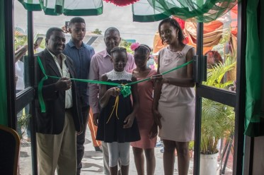 Dr. Lowell Porter and the Younge's Family cuts the ribbon to signify the official opening of Tidy Up Detergent Refill Center