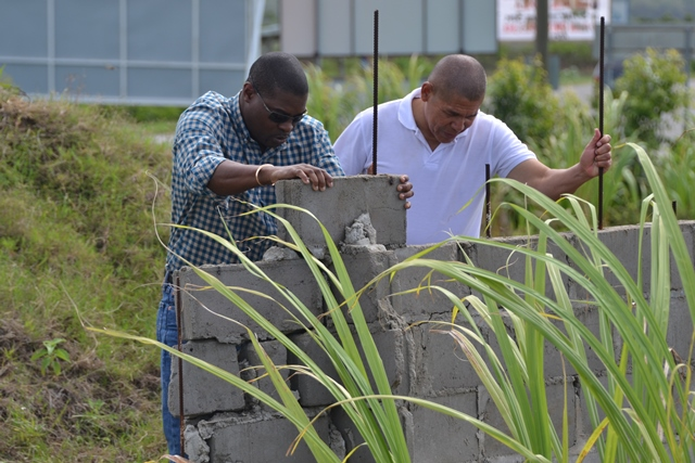 Ministers David Patterson and George Norton testing the strength of the crumbled monument