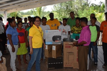 Minister within the Ministry of Indigenous Peoples' Affairs Valerie Garrido-Lowe (left) presenting equipment to Toshao of Imbetero and HEYS participants