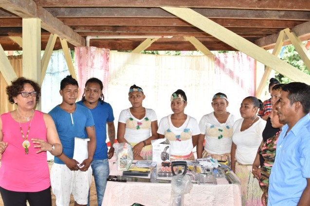 Minister within the Ministry of Indigenous Peoples' Affairs Valerie Garrido-Lowe (left) presenting equipment to CDC chairman of Eclipse Falls Emanuel Henry (far left) and HEYS participants