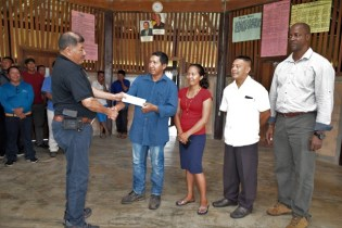 Arnold Moses, Senior Councillor, Wowetta Village receiving a cheque from Minister of Indigenous Peoples' Affairs, Sydney Allicock in the presence of Permanent Secretary, Alfred King and other councillors.