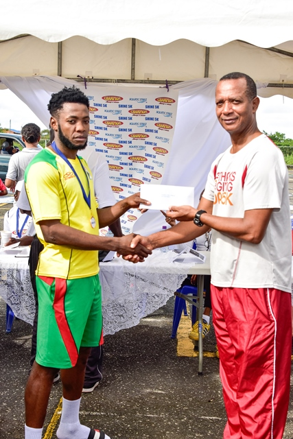 Winston Missigher receiving his prize from President of the Athletics Association of Guyana (AAG) Aubrey Hutson.