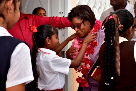 Minister of Public Telecommunications, Catherine Hughes smiles as a pupil places a garland around her neck.