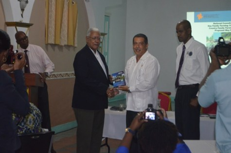 Minister of Agriculture, Noel Holder receives a copy of the report from IICA's representative, Wilmot Garnett as Sustainable Development Specialist, Arnold De Mendonca looks on.