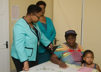 Minister Volda Lawrence interacts with a patient at the Dr. CC Nicholson Hospital.