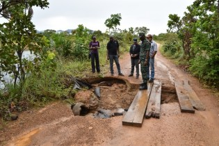 Director General of the Civil Defence Commission (CDC), Lieutenant Colonel Kester Craig and other officers examine a damaged section of the roadway.