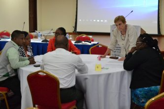Consultant Joanne Tompkins interacts with education officials