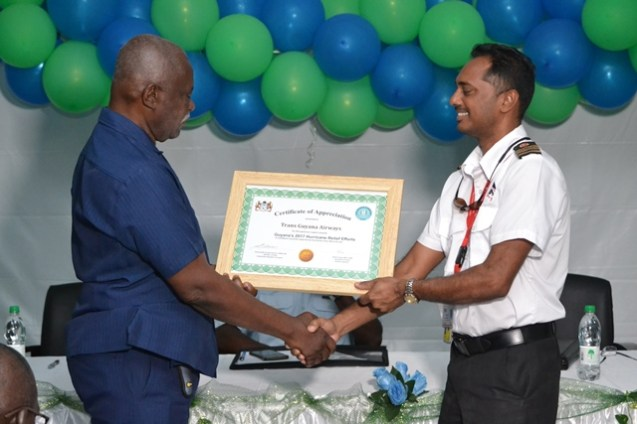 Minister of Citizenship, Winston Felix hands over the award of appreciation to a representative of Trans Guyana Airways.