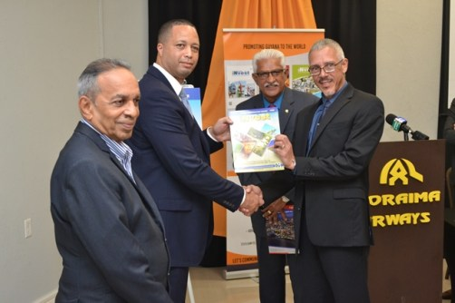 Chief Executive Officer (CEO) of GO-Invest, Owen Verwey [second from left] presents a copy of the magazine to Minister of Business, Dominic Gaskin [right]. [Also, in photo] Managing Director for Advertising and Marketing Services, Lokesh Singh [centre] and Chairman of the Private Sector Commission, Edward Boyer [extreme left].