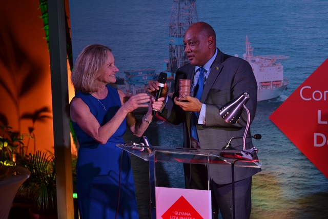 Exxon's Vice President, Lisa Waters presenting a symbolic barrel to Minister of Natural Resources, Raphael Trotman.