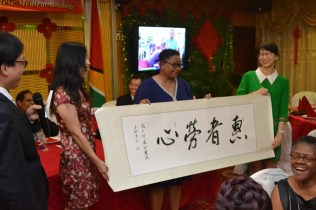 Minister of Public Health, Hon. Volda Lawrence receives a token of appreciation from members of the 13th Chinese Medical Brigade.