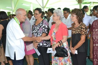 Father Malcolm Rodrigues greets one of the members of the St. John's Association of Guyana.