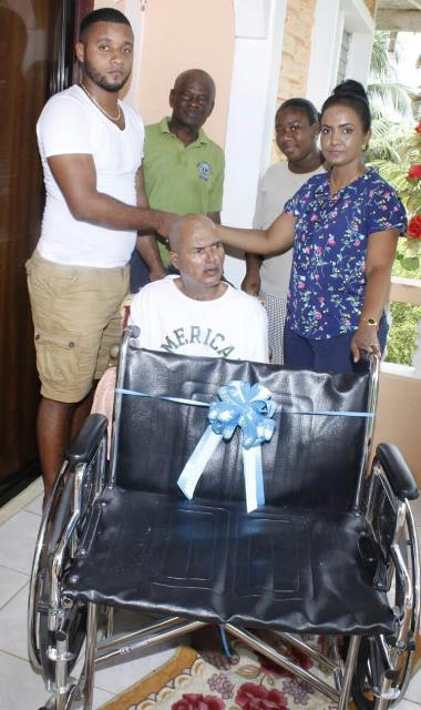 Deputy-Mayor Nageswari Kamal Persaud presents the wheelchair to Michael White on behalf of his father Raymond White (seated). Also, in photo Councillor and Lion's Club member Lloyd Garraway and Monesha Subryan.