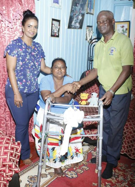 Deputy-Mayor Nageswari Kamal Persaud and Councillor Lloyd Garraway presenting Agnes Dass with a walker.